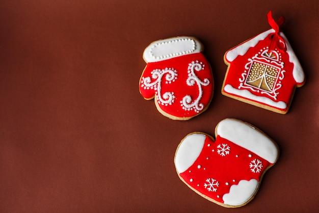 Fundo de férias de ano novo de natal, biscoitos de gengibre vermelho e cones na mesa vermelha escura. copie o espaço