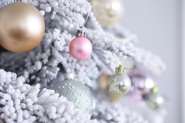 Fundo de férias de natal. bugiganga prateada e colorida pendurada em uma árvore decorada com bokeh e neve, copie o espaço.
