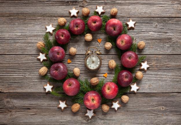 Fundo de férias de natal com cookies, maçãs vermelhas, galhos de árvore do abeto, relógio vintage,