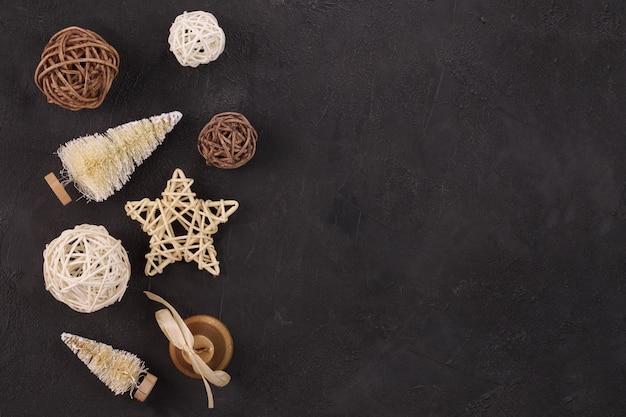 Fundo de férias de natal: estrelas de vime e bolas em um fundo preto.
