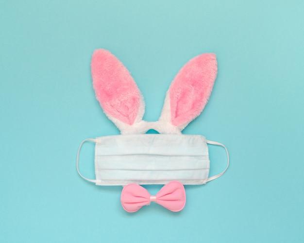 Fundo de férias de páscoa com orelhas de coelho rosa, máscara médica e arco sobre um fundo azul. conceito de quarentena. postura plana.