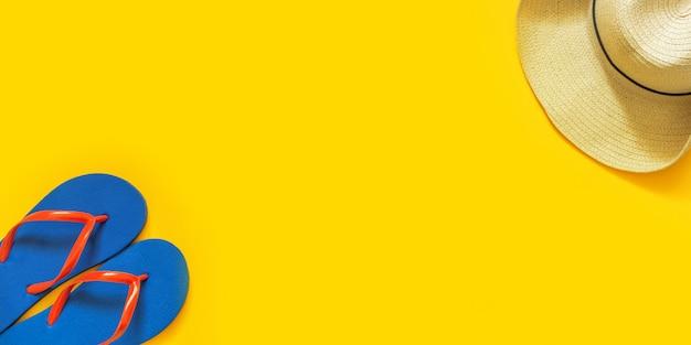 Fundo de férias de viagens. flip-flops, chapéu em um fundo amarelo.
