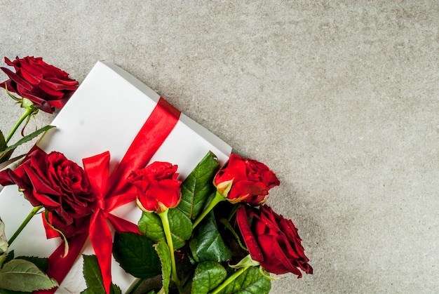 Fundo de férias, dia dos namorados. buquê de rosas vermelhas, amarre com uma fita vermelha, com caixa de presente embrulhada. em uma mesa de pedra cinza, copie a vista superior do espaço