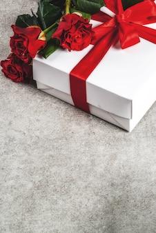 Fundo de férias, dia dos namorados. buquê de rosas vermelhas, amarre com uma fita vermelha, com caixa de presente embrulhada. em uma mesa de pedra cinza, copie o espaço