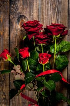 Fundo de férias, dia dos namorados. buquê de rosas vermelhas, amarre com uma fita vermelha. em uma mesa de madeira