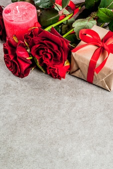 Fundo de férias, dia dos namorados. buquê de rosas vermelhas, gravata com uma fita vermelha, com caixa de presente embrulhada e vela vermelha. em uma mesa de pedra cinza, copie o espaço