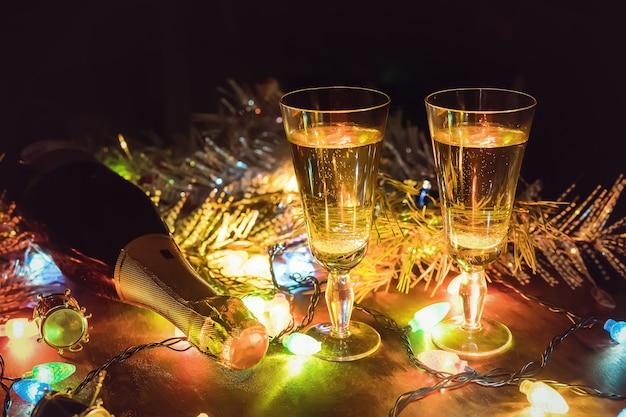 Fundo de férias. duas taças com champanhe e garrafa sobre uma mesa de madeira decorada com acessórios de natal para celebrar o ano novo e o natal. noite romantica. dia dos namorados