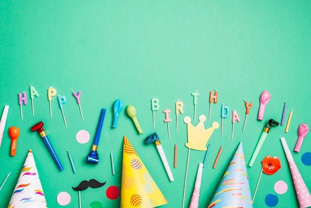 Fundo de festa de aniversário com chapéus de festa; adereços; balões; soprador de chifre e velas em pano de fundo verde