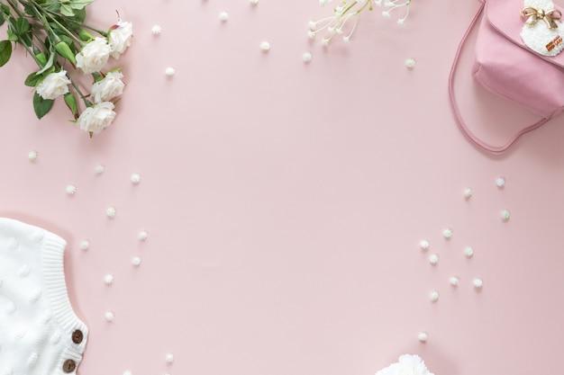 Fundo de flores de chá de bebê com acessórios de menina em fundo rosa com espaço de cópia para texto, vista de cima, plano leigo