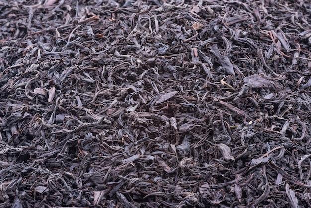 Fundo de folhas de chá secas de cor escura.