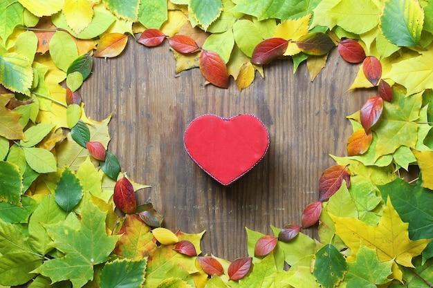 Fundo de folhas de outono em forma de coração na mesa de madeira