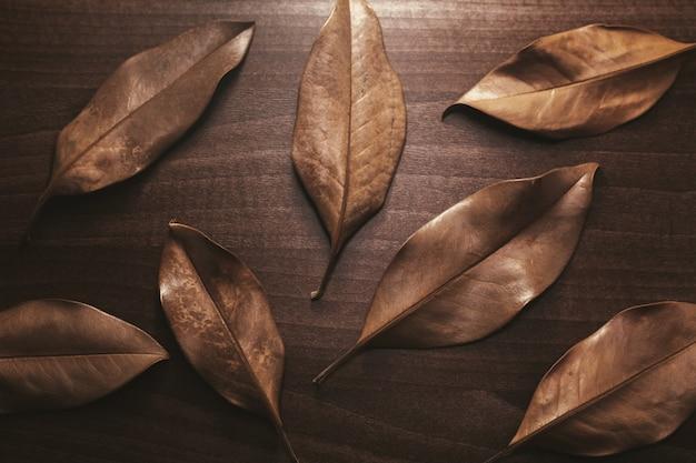 Fundo de folhas secas e marrons em uma mesa de madeira