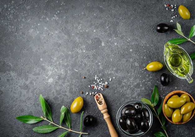 Fundo de fronteira de alimentos de azeitonas verdes e pretas com ramos. vista superior, copie o espaço.