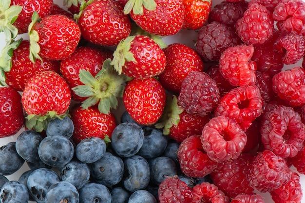 Fundo de frutas frescas saborosas. morangos, mirtilos e framboesas fecham a vista superior Foto Premium