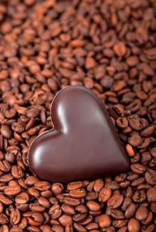 Fundo de grãos de café e coração com doces em forma de coração