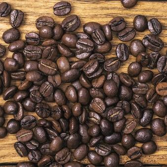 Fundo de grãos de café torrados é marrom em tábuas de madeira