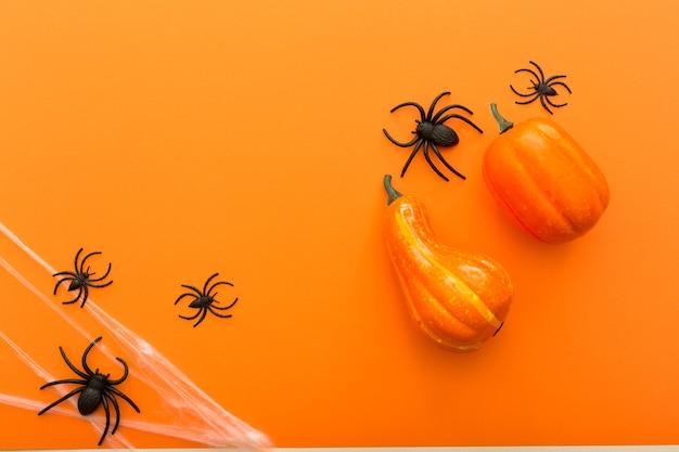 Fundo de halloween com abóboras, teia de aranha e aranhas como símbolos do halloween no fundo laranja. conceito de feliz dia das bruxas. quadro, armação.