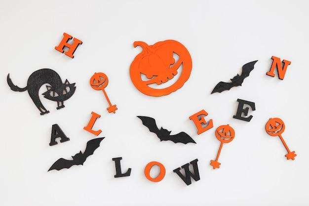 Fundo de halloween com as letras halloween, abóbora ou jack-o-latern, gato preto e morcegos