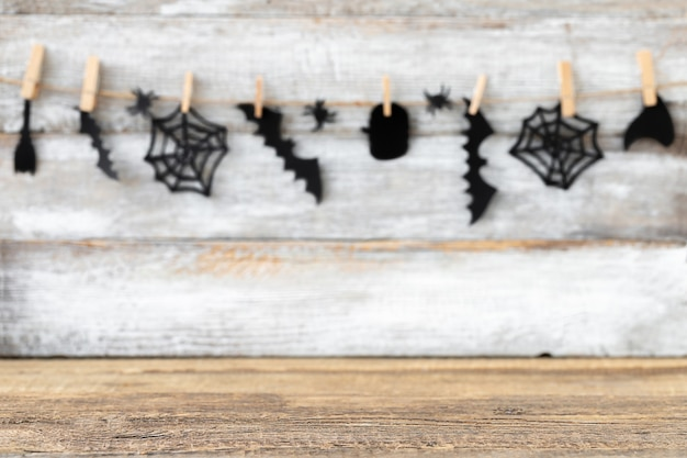 Fundo de halloween com guirlanda desfocada de acessórios pretos e superfície de madeira focada