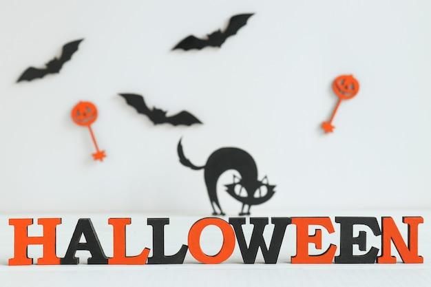 Fundo de halloween com letras laranja e pretas halloween, gato preto e morcegos. foco seletivo