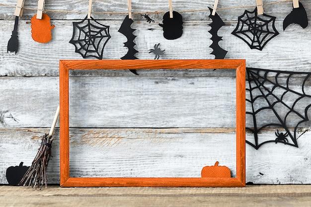 Fundo de halloween com moldura laranja e acessórios de papel preto em uma superfície de madeira