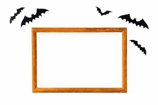Fundo de halloween com moldura laranja no meio e morcegos pretos em uma superfície cinza