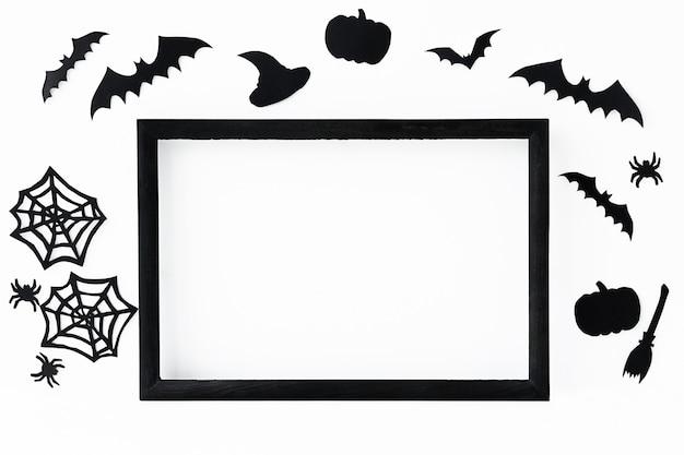 Fundo de halloween com moldura preta e acessórios de papel preto para férias em uma superfície cinza