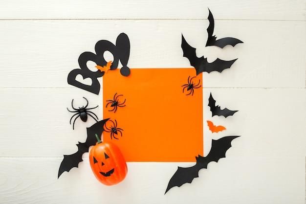 Fundo de halloween com morcegos de papel, aranhas, jack-o'-lantern em fundo branco de madeira. decorações do feriado de halloween. camada plana, vista superior, espaço de cópia. maquete de convite de festa, celebração.