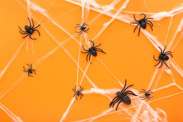 Fundo de halloween com teia de aranha e aranhas como símbolos do halloween no fundo laranja. conceito de feliz dia das bruxas.