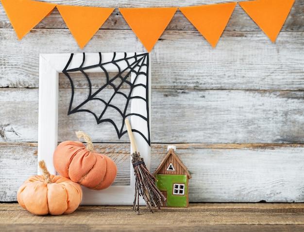 Fundo de halloween com vassoura de casa pequena de teia de abóboras e guirlanda de bandeiras em uma superfície de madeira
