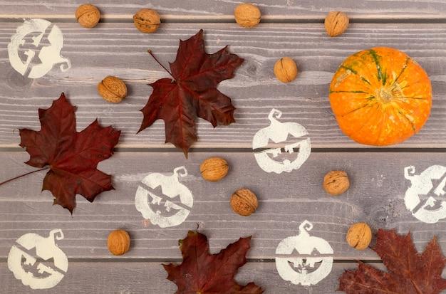 Fundo de halloween de abóboras maduras, folhas caídas e símbolos de halloween estampados.