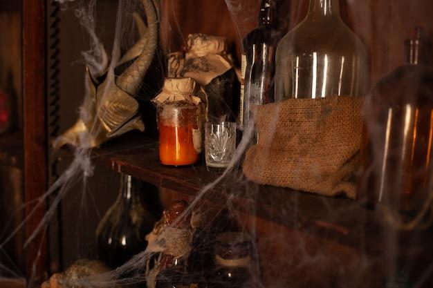 Fundo de halloween prateleiras com ferramentas de alquimia garrafa de teia de aranha de crânio com velas de veneno espaço de trabalho do bruxo quarto assustador