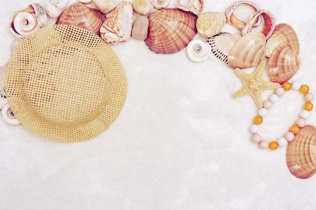 Fundo de horário de verão com conchas do mar, pedras do mar, chapéu de palha, pulseira feminina