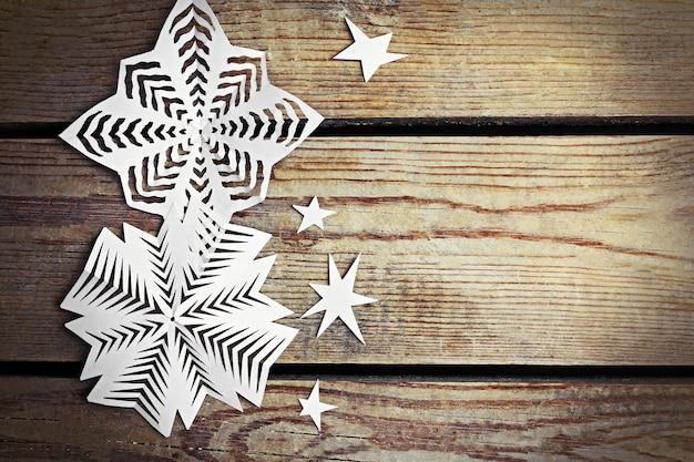 Fundo de inverno com flocos de neve de papel feitos à mão em fundo de madeira