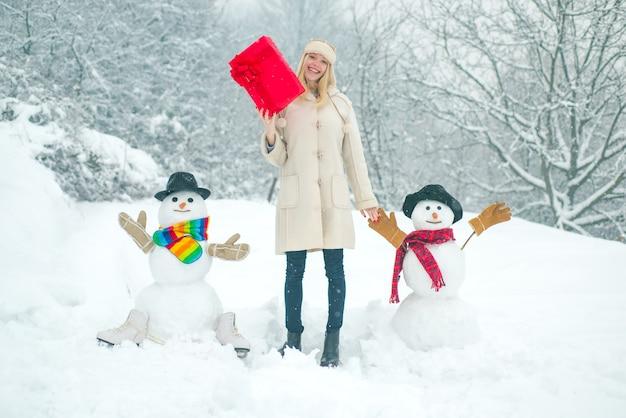 Fundo de inverno com flocos de neve e garota de boneco de neve brincando com boneco de neve em winter park winter woman