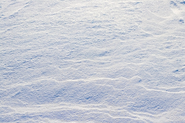 Fundo de inverno com terreno coberto de neve após uma nevasca. neve no chão com tempo ensolarado