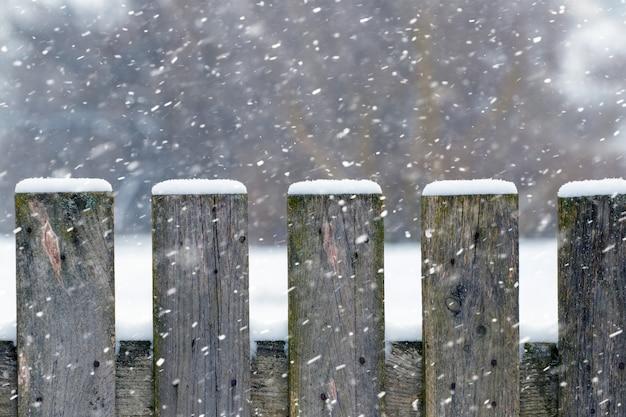Fundo de inverno com uma cerca de madeira coberta de neve durante uma nevasca