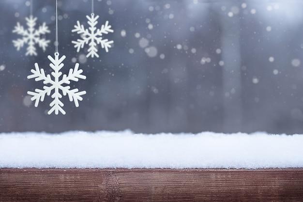 Fundo de inverno de natal com neve de base de madeira e flocos de neve pendurados