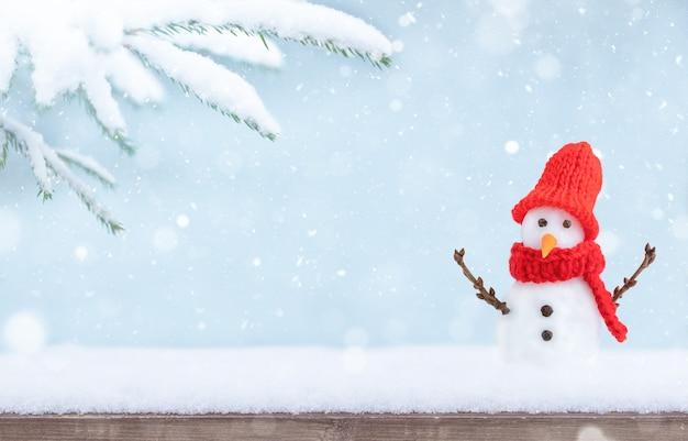 Fundo de inverno de natal com neve de base de madeira galho de árvore de natal e boneco de neve