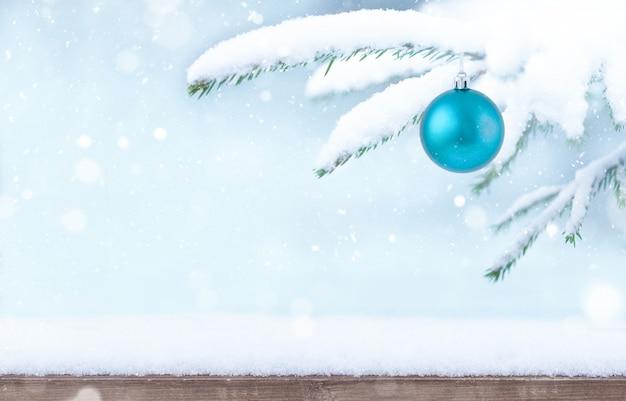 Fundo de inverno de natal com neve de base de madeira galho e enfeite de árvore de natal