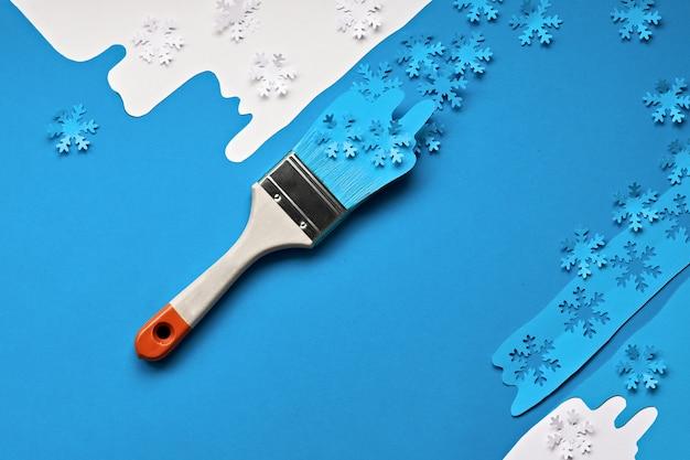 Fundo de inverno em azul e branco com pincéis carregados com flocos de neve de papel