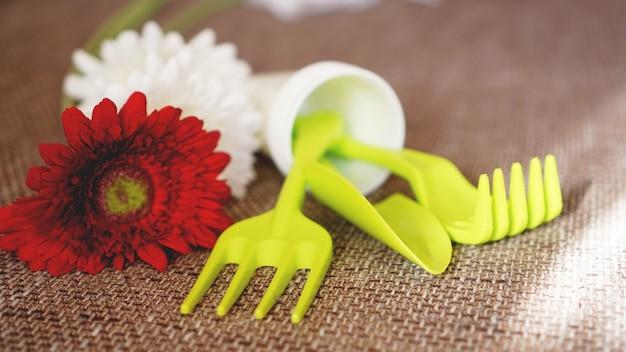 Fundo de jardinagem. ferramentas e flores verdes de jardinagem - foco suave