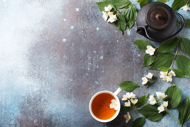 Fundo de jasmim chá com bule, folhas e flores em textura escura, vista superior, espaço de cópia