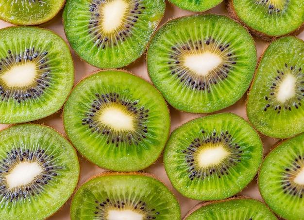 Fundo de kiwi verde fresco. cama plana, vista superior, conceito de comida. quadro de comida com espaço de cópia para o seu texto. bandeira. textura de círculos verdes de kiwi