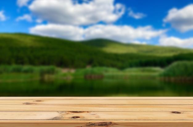 Fundo de lago e colinas verdes com expositor de mesa de madeira