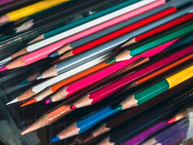 Fundo de lápis de cor. feche várias cores do velho em lápis de cor usados na mesa de vidro no estúdio de arte, estilo de tom vintage. ferramentas de artista para fazer obras de arte.