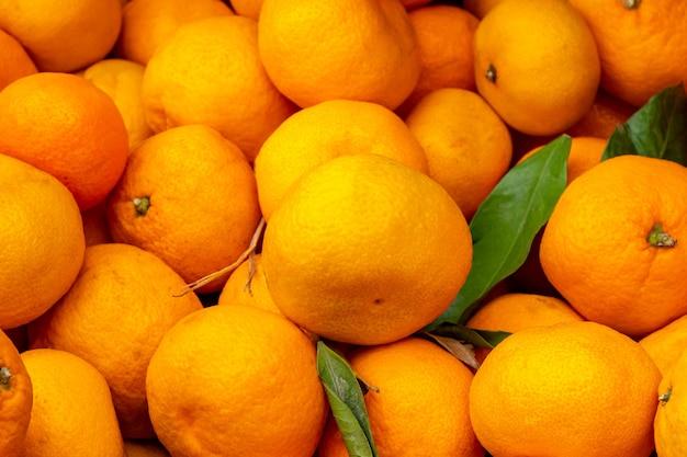 Fundo de laranjas de frutas de tangerinas. mercado fresco saudável. doce suculento Foto Premium
