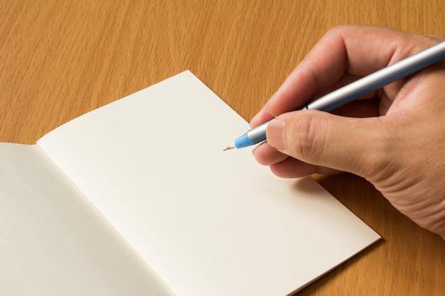Fundo de livro de nota em branco aberto com caneta de preensão de homem de negócios para escrever