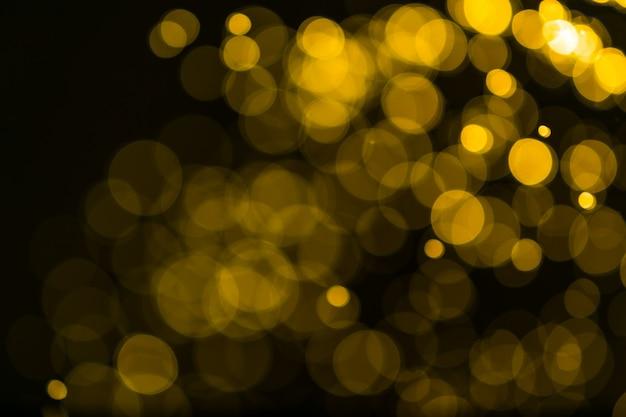 Fundo de luzes vintage de brilho. ouro escuro e preto. desfocado