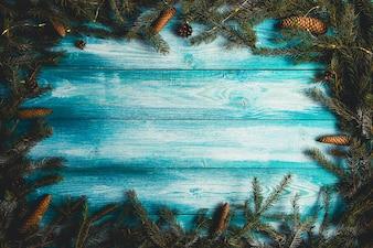 Fundo de madeira azul do Natal com ramos do abeto e luzes de Natal.